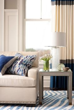 color blocked drapes, zebra rug and neutral sofa with blue throw pillows
