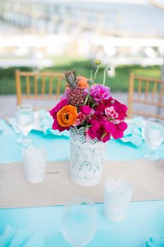 Bougainvillea, ranunculi, and a pink pineapple in a papel picado vase | Photo by Jessica Bordner | Floral design by Lara's Theme