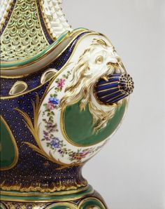 Located 2015 in the Green Drawing Room of Buckingham Palace, London, UK. 2 of 4 pins of Porcelain Pot-pourri vase & cover made by Sèvres porcelain factory in 1758.  Close view of  the ends (sides) of the vase in the form of a bowsprit projecting from the jaws of a marine monster. Purchased by George IV (1762-1830) UK, Uncle of Queen Victoria (1819-1901) UK.