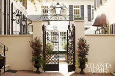 An elegant gate leads to the beautiful front door of a house that's sited within mature landscaping. // Atlanta, GA