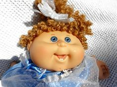 Blonde curly hair blue eyes cabbage patch with satin blue dress, showing bottom teeth