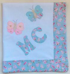 Manta em tecido piquet 100% algodão, com iniciais do nome do bebê personalizada e patch aplique de borboletas com pérola.    Tamanho 80x90cm    **As cores para o tecido do barrado e o tema para o aplique podem ser escolhidos**