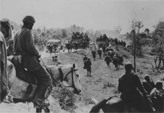 WWII - Greek cavalry look at a convoy of trucks.