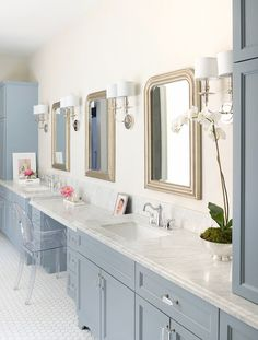 Amazing bathroom features three silver leaf beaded mirrors, Ballard Designs Louis Mirrors, flanked by 2-light sconces over blue washstands topped with marble flanking blue, drop-down vanity paired with Ghost Chair atop vintage hex tiled floor.