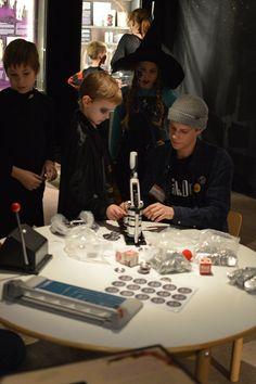 Rintanappikoneella saa tehdä lepakkorintanapin muistoksi illasta. OSAO:n opiskelijat auttavat pieniä museovieraita. Luuppi, Oulu (Finland)