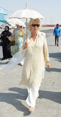 Camilla, Duchess of Cornwall holds a parasol as she tours the International Humanitarian City to see the innovation and best practice in humanitarian aid delivery on November 2016 in Dubai, United Arab Emirates. English Royal Family, Camilla Parker Bowles, November 8, Duchess Of Cornwall, Royal House, Prince Of Wales, British Monarchy, Lady Diana, Prince Charles