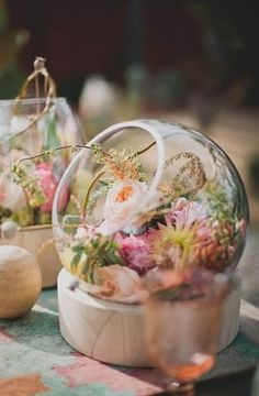 i love these glass bowls filled with pretty petals for an unexpected and sweet centerpiece