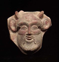 SUPERB ETRUSCAN ANTEFIX, ca. 6th-5th century BC. The antefix with the facing head of the god Pan with bushy beard and goat horns, the face with original red pigment and the beard, eyebrows and pupils of the eyes with the original black. 5.5 x 6 inches. The face intact and in excellent condition. Cf. Christie's Dec. 1998, #82 for a very similar antefix in inferior condition estimated at $10,000-$15,000. A wonderful early piece of impeccable style.