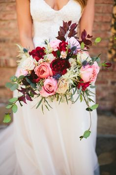rich fall colors in a loose bridal bouquet of red charm peony, romantic antike garden rose, dark red rose,white majolik spray rose, blue thistle, light pink ranunculus, white astilbe, purple plum branch, peach stock, cappuccino rose, seeded eucalyptus, willow eucalyptus & jasmine vine.