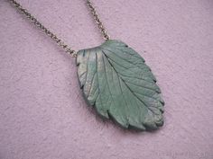 This is a handmade polymer clay pendant necklace. Fixed on a bronze tone metallic chain (it can not be moved or taken off of it).  Leafs
