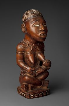 Seated Female Nursing Child Artist: Master of the Boma-Vonde Region Date: 19th–early 20th century Geography: Democratic Republic of the Congo, Kai Kuinba village [?]; Republic of the Congo; Cabinda, Angola Culture: Kongo peoples; Yombe group Medium: Wood, kaolin, glass Dimensions: H. 10 3/4 in. (27.3 cm), W. 5 in. (12.7 cm), D. 4 in. (10.2 cm)