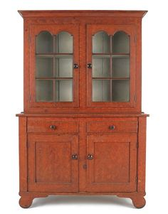 """Realized Price: $16590 Lehigh Valley, Pennsylvania painted pine Dutch cupboard, ca. 1840, in two parts, the upper section with two six-lite doors, the base with two drawers over two sunken panel doors, all resting on scrolled feet, retaining its original red flame grained surface, 84"""" h., 51 1/2"""" w., 19 1/2"""" d."""