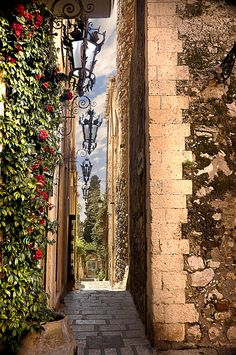 Side street in Taormina, Sicily Messina ~ Taormina is a comune and small town on the east coast of the island of Sicily, Italy, in the Province of Messina, about midway between Messina and Catania.