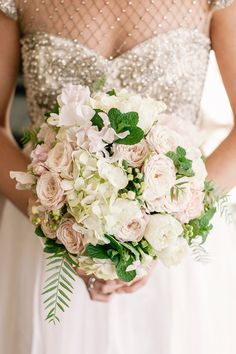 Posh Bridal Bouquet Comprised Of: White Ranunculus, White Sweet Pea, Cream Cabbage Roses, White Hydrangea, Greenery/Foliage