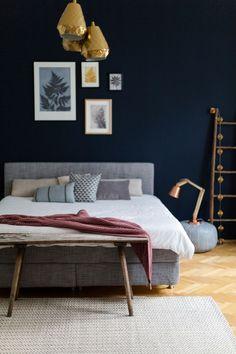 Inspiration Umgestaltung oder neues Schlafzimmer mit grauem Boxspringbett. Dunkle Wandfarbe im Schlafzimmer wird aufgelockert durch helles Bettzeug und eleganter Look durch die goldenen Hängelampen.