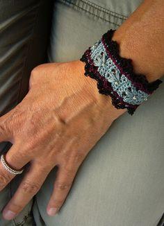Gehäkeltes Armband, bestickt mit Rocailles, verschlossen mit zwei schönen Glasschliffperlen.  *UNIKAT*  Länge ca. 17 cm Breite ca. 3,5 cm
