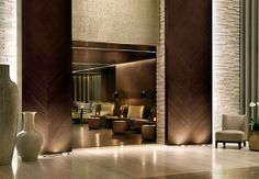 Lobby at The Istanbul Edition Hotel, by HBA - double height rosewood doors, gold/bronze mosaic tiles on the walls