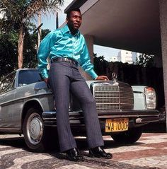 Pele, one of the stars of the victorious Brazilian 1970 World Cup winning team in Mexico, pictured wearing trousers and a bright shirt as he poses in front of a Mercedes car