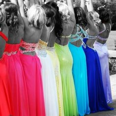 Black and white picture of friends in colored prom dresses.