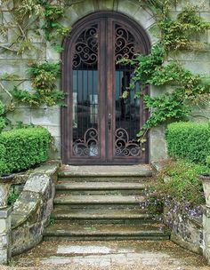Perfect entryway for a garden lovers dream home.  How can you not love a hand forged, wrought iron door? Entry doors. Front door.  Dream home. Wrought iron door.