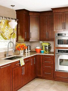 Mainstream Beauty: Rich cherry cabinets with oversize hardware, a glass-tile backsplash, and quartz countertops are popular and easily found finishes that create a refined, upscale kitchen.: