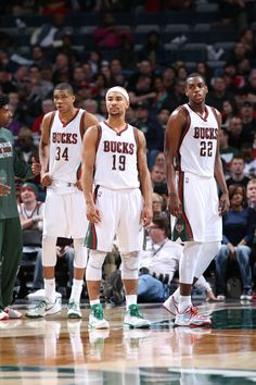 Giannis Antetokounmpo #34, Jerryd Bayless #19 and Khris Middleton #22 of the Milwaukee Bucks stand on the court during a game against the New Orleans Pelicans on March 9, 2015 at the BMO Harris Bradley Center in Milwaukee, Wisconsin. (Photo by Gary Dineen/NBAE via Getty Images)