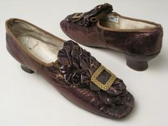 1874-1876 Bronze wedding shoes with rounded square toes and elastic gusset at front, instep entirely covered by a rosette of bronze kid extending upwards from the toe. Oblong basketwork buckle is on each toe. Manchester Art Gallery