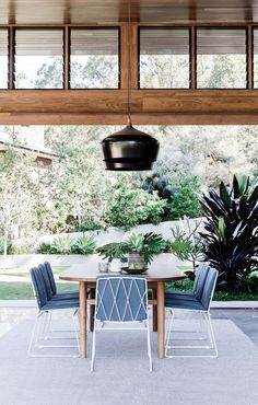 Sliding doors retract completely on both sides of the space to create the feeling of an outdoor room. Custom-made dining table.'Seb' dining chairs, from Jardan. Coco Flip 'Coco' pendants, from Cult. Rug, Armadillo & Co.