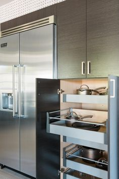 Pull out shelves in the long cabinets beside the double wide refrigerator hold pots and pans within reach of the cook.