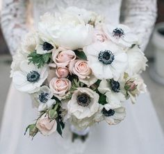 A textured clutch bouquet of cream hydrangeas, white anemones, pale blush garden roses, grey succulents, white sweet peas, white ranunculus, ivory spray roses, and dusty miller wrapped in ivory ribbon with the stems showing