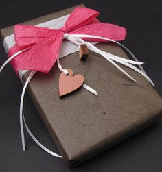 Wrap your gift in a great neutral paper, then embellish with bright ribbon and decorative elements. #giftwrap