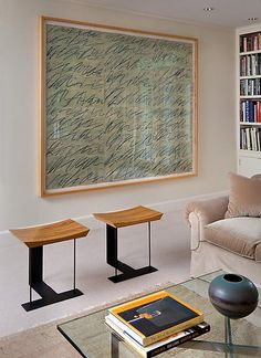 1920's stools by the legendary designer Pierre Chareau vie for attention with a work on paper by another legend, American artist Cy Twombly in the living room.