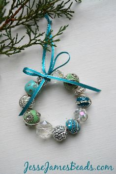 Ho! Ho! Ho! Here's a quick ornament idea to make with your favorite Jesse James bead strand or loose beads. Trim the tree or top a package with these sweet beaded wreaths! (materials and supplies at the end of this post)First, select your beads. The boho style beads make for unique and festive ornaments!String all …