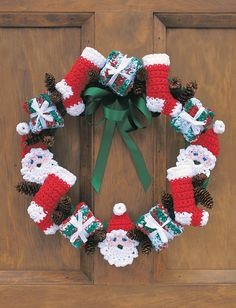 Free Crochet Christmas Wreath Pattern--Ho ho ho! Jolly Santas, wrapped presents, and stockings circle this very Christmas wreath. Crocheted Free Crochet Wreath Pattern--. Plus there won't be pine needles to pick up!