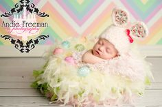 Newborn baby girl in pink, green, and yellow feather nest with pink Easter bunny hat in front of pastel rainbow chevron backdrop.   www.TheAthensNewbornPhotographer.com