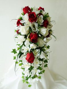 Diana - A large, traditional shower bouquet featuring deep red roses as the focal flowers with white mini cymbidium orchids, lisianthus, roses, trailing ivy and beargrass.