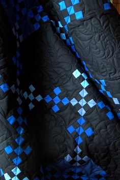 Modern Amish quilt design in bright blue neon squares on a black background (colors!)