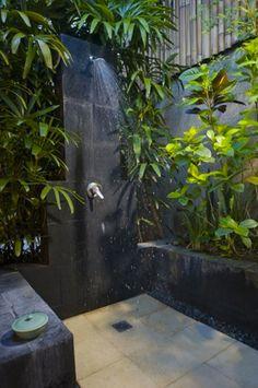 Douche extérieure de jardin dans patio pierre à côté maison
