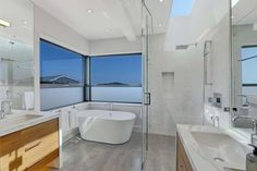 The master bathroom boats a soaking tub and vanities with waterfall edges. Photo: JASON WELLS