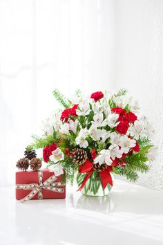 White alstroemeria and Douglas fir are mixed with pinecones and red berries in a clear bowl decorated with red satin ribbon. Christmas Flowers, Christmas Gifts, Holiday, Local Florist, Christmas Centerpieces, Let It Snow, Red Berries, Flower Arrangements, Celebrations