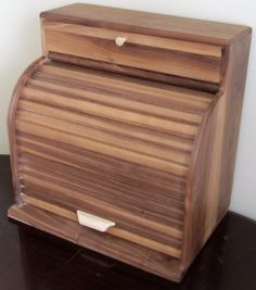 Finished with our own butcher block and cutting board treatment, This large handmade breadbox features a maple, slide out cutting board and a top compartment with a drop down door for storing small ro