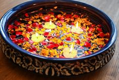 A Rajasthani blue work urli with fresh flower petals and floating candles for Diwali