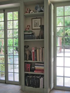 This smallish book case makes the perfect divider between these lovely French doors.  The depth also allows it to serve as the perfect place to draw back the shutters.  Look by Atlanta Designer, Margaret Kirkland.
