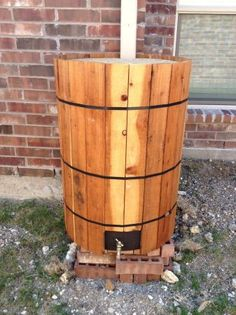 Rain Barrel.. good idea to cover up an ugly barrel. could use fence pickets or pallet boards with nautical rope