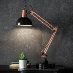 Stylish table lamps with an industrial style featuring an adjustable frame and cone-shaped shade.