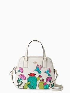"take the scenic route: this cream-colored handbag is decorated with a picturesque desert scene, complete with three-dimensional appliqued leather blossoms and studded ""needles"" on the cacti, for a look that really stands out."