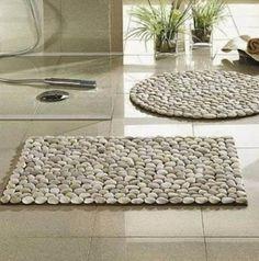 Com alguns seixos e um tapete com antiderrapante, você poderá criar seu próprio tapete de pedras.
