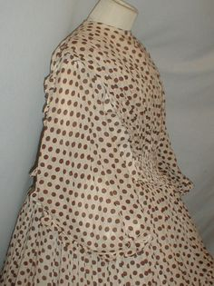 "1860s dotted brown & beige cotton print dress, self-fabric ruffle on sleeve, fan pleated, ruching at front waist; piping at neck, armscyes & waist; bodice lined with cotton, back hook & eye closure; skirt has 4 wide ruffled tiers, skirt unlined except wide band of cotton at hem; no underarm discoloration, sturdy; bust: 34""; waist: 26""; skirt length: 38""; hem width: 120"""