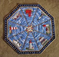 "9-28-15 ""Lighthouses All Around""    My design using machine embroidered lighthouses and compass.  Machine quilted.  Actual lighthouses, name of each along the left side of each triangle."