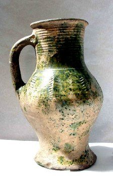 Baluster jug; green glaze; rim with lip; strap handle with groove; cylindrical neck; biconical body with flared foot; thumbed base; wheatear stamped boss decoration.1240-1360 (circa)Kingston Ware (all objects)